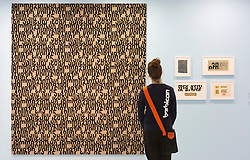 "© Licensed to London News Pictures. 21/10/2013. London, England. A museum worker stands in front of letters by Gunnar Aargard Anderson. The Exhibition ""Pop Art Design"" opens at the Barbican Art Gallery/Barbican Centre running from 22 October 2013 to 9 February 2014. The exhibition brings together 200 works by 70 artists and designers including Peter Blake, Andy Warhol and Roy Lichtenstein. Photo credit: Bettina Strenske/LNP"