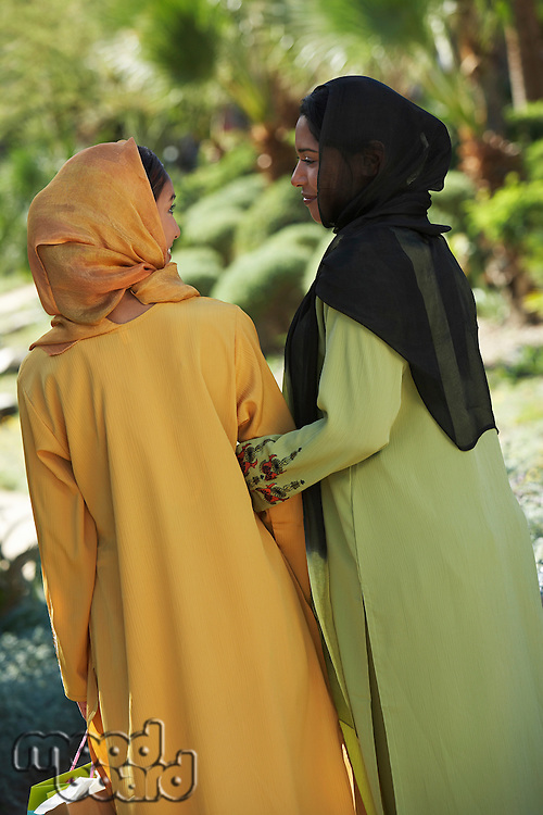 Two muslim woman in traditional clothing, back view