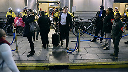 Commuters make a way through the Bike Patrol Officer outside the west entrance at 30th St. Station, on Thursday. (Bastiaan Slabbers for NewsWorks)