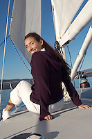 Young woman sitting on deck of sailboat (portrait)