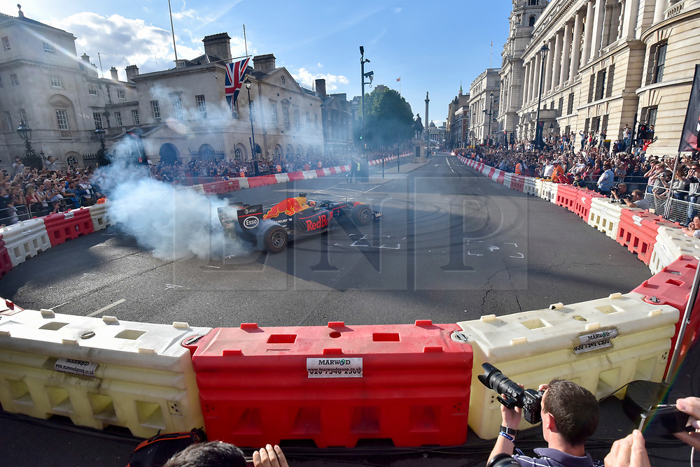 """© Licensed to London News Pictures. 12/07/2017. London, UK.   A driver performs a """"doughnut"""" during a parade of Formula One cars taking place around a circuit passing Trafalgar Square and Whitehall during a promotional event called F1LiveLondon ahead of the British Grand Prix at Silverstone.   Photo credit : Stephen Chung/LNP"""
