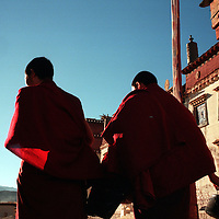 "ZHONGDIAN COUNTY, DECEMBER 19, 2000: Tibetan walk through a gate of Songzanlin monastery, Yunnan province , December 19, 2000..Zhongdian county is believed to be part of the areas on which James Hilton's famous novel "" lost Horizon""- a description of Shangri-La- is modelled.. ."