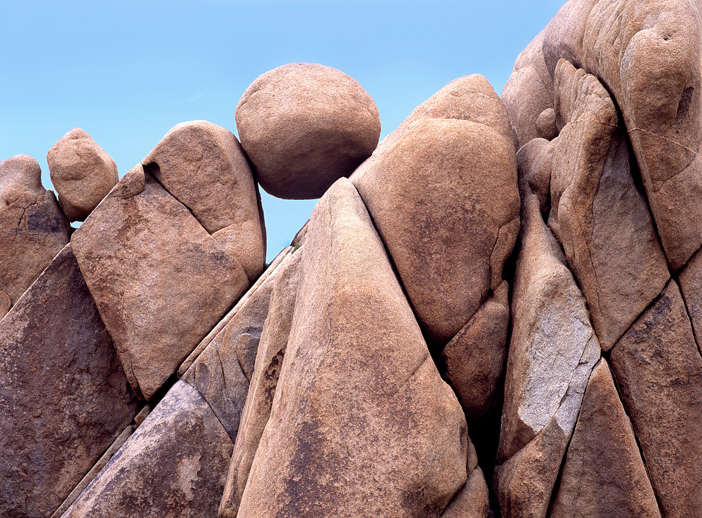 A large round rock balances on a bed of rocks in Joshua Tree National Park in California.