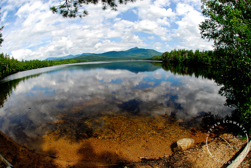 New Hampshire lake and mountain view. Cloud Reflect in peaceful mid summer water.