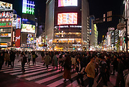 Neon signs above crowds at the Shibuya Crossing in Tokyo, Japan