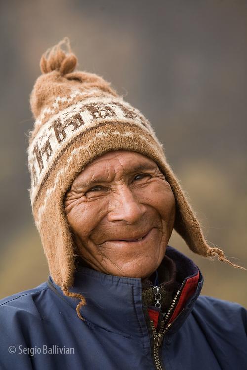 A local Aymara Indian smiles toward the camera in the mountains outside of Sorata, Bolivia