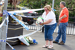 "© Licensed to London News Pictures. 27/06/2012. Oldham , UK. Flowers and a teddy bear are left by a crying couple (pictured) at a makeshift shrine to two year old Jamie Heaton , who died in the exploion. The card attached to the flowers is signed off "" hugs n kisses Auntie Syl and Geoff "". A large explosion , believed to be caused by gas , has brought down at least one house in an Oldham terrace . . Photo credit : Joel Goodman/LNP"