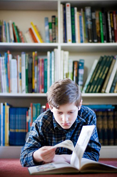 Ten year old boy reading a book, England, United Kingdom.