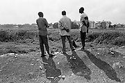 Nubian youth look out over the remains of the Nairobi Dam. What was once a lake where Nubians went fishing and swimming is now a swampy and smoldering landfill and garbage dump.