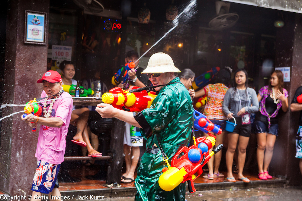 14 APRIL 2013 - BANGKOK, THAILAND:  A tourist wearing a bathrobe participates in a Songkran water fight on Soi Nana on April 14, 2013 in Bangkok, Thailand. The Songkran festival is celebrated in Thailand as the traditional New Year's Day from 13 to 15 April. The throwing of water originated as a way to pay respect to people and is meant as a symbol of washing all of the bad away. PHOTO BY JACK KURTZ