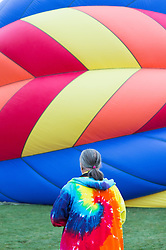 man in a colorful jacket at a colorful hot air balloon festival in New Mexico
