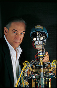 "Alvaro Villa translated his boyhood love of electronics into AVG, an animatronics company he founded in the Los Angeles, California, area. Today he takes great pleasure in showing off animatronic figures like the Crypt Keeper or Little Man, the hip figure (with Villa) that ""represents"" the company at trade shows. Wearing a baseball cap and sneakers, it tirelessly delivers a humorous prerecorded spiel that is synchronized with a video on a screen behind it. From the book Robo sapiens: Evolution of a New Species, page 208."