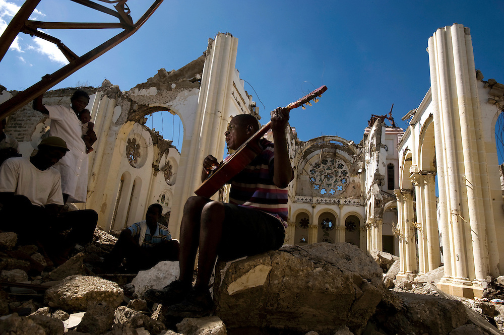 "In the ruins of the Cathedral of Port au Prince,  Olince Calixte, a blind man living in a makeshift camp nearby  sings ""Haiti is Always Crying""."