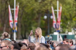 © Licensed to London News Pictures. 02/05/2015. London, UK. A girl takes a photo in the crowd, as in keeping with tradition, the royal birth announcement of the Duke and Duchess of Cambridge's second child, a daughter, born at 8.34am, today, 2 May 2015, is posted on an easel outside Buckingham Palace.  The document is signed by the the delivery team at St Mary's Hospital in Paddington - led by Alan Farthing, the royal surgeon-gynaecologist . Photo credit : Stephen Chung/LNP