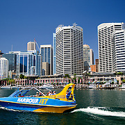 A tourist jet boat heading out from Darling Harbour in Cockle Bay with the skyline of the Central Business District of Sydney in the background.