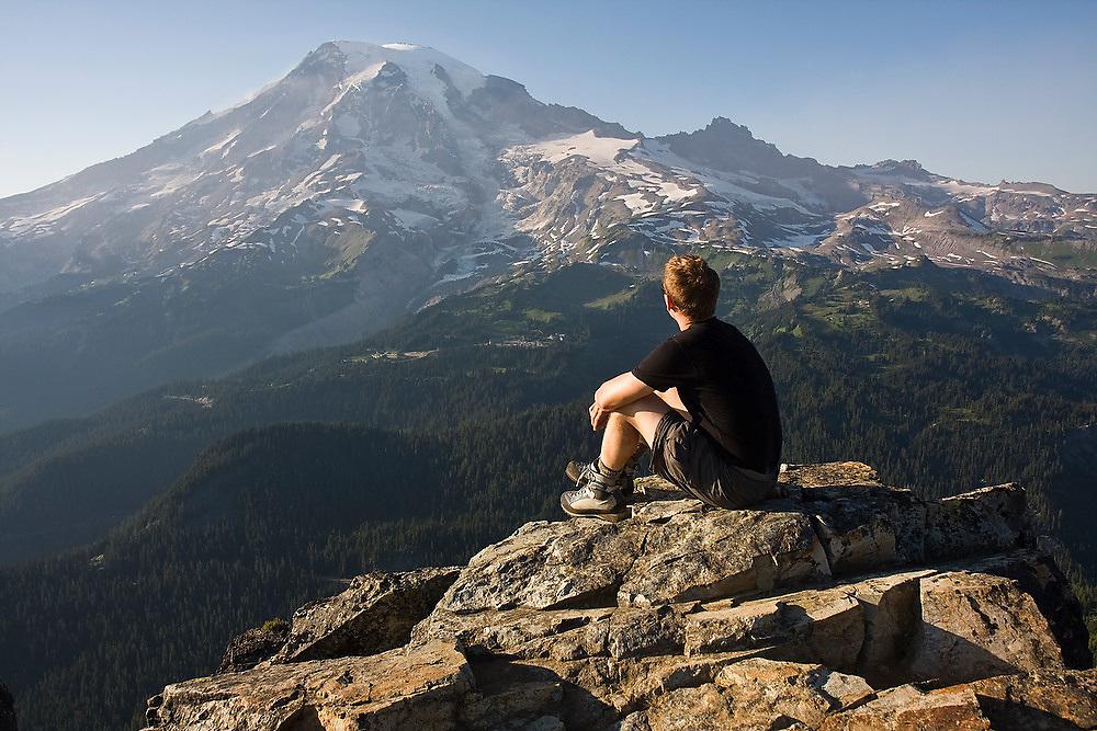 Climber Ian Derrington sits on the summit of Pinnacle Peak enjoying the views of Mount Rainier during a traverse of the Tatoosh Range in Mount Rainier National Park, Washington.