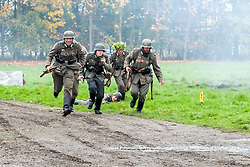 World War Two Re-enactors portraying panzer grenadiers carrying K98 Rifles run to take up positions during a battle battle re-enactment in on Pickering Showground<br />