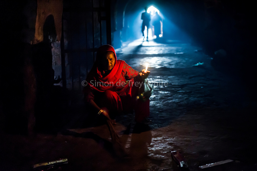 26th November 2015, New Delhi, India.  A woman sweeps the floor in the ruins of Feroz Shah Kotla in New Delhi, India on the 26th November 2015<br /> <br /> PHOTOGRAPH BY AND COPYRIGHT OF SIMON DE TREY-WHITE a photographer in delhi<br /> + 91 98103 99809. Email: simon@simondetreywhite.com<br /> <br /> <br /> The13th century fortress-city of Firoz Shah Kotla in Delhi is thronged weekly with thousands of supplicants seeking favour from supernatural beings of smokeless fire, - Djinns. These magical entities also known as Jinn, Jann or Genies spring from Islamic mythology as well as pre-Islamic Arabian mythology. They are mentioned frequently in the Quran and other Islamic texts and inhabit an unseen world called Djinnestan. Believers, mostly Muslim but from other faiths too, circumnavigate the ruins clutching dozens of photocopied requests, flower petals, incense, and candles. They visit the numerous niches and alcoves in the catacombs said to be occupied by different djinns and greet and salute the invisible occupants with offerings.  A copy of their requests, often with detailed contact information, photographs and even police reports to bolster the case is left with the &lsquo;Baba&rsquo; before moving on to the next where the procedure is repeated - like making applications at different departments of a bureaucracy