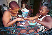 MARCH 19, 2001 - HAVANA, CUBA: A woman gives her neighbor a manicure in the front room of her apartment in the centro section of Havana, Cuba, March 19, 2001. Many Cubans use small in home businesses to supplement their state salaries.  PHOTO BY  JACK KURTZ     ECONOMY  POVERTY   LABOUR LABOR  UNEMPLOYMENT   WOMEN