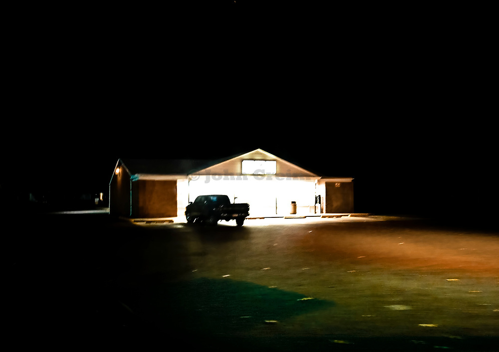 Pick-up parked in remote convenience store parking lot late at night.