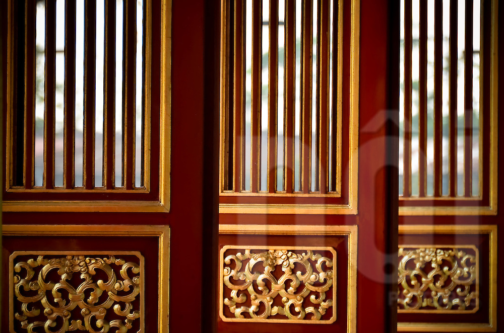 Detail of doors that have just been renovated with fresh red painting and gilding in the Hue Citadel. Vietnam, Asia