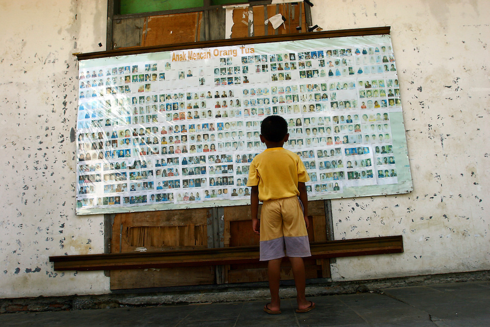 Yound child checks on the board inside the Long barracks for lost relatives. @ Martine Perret. February 2006