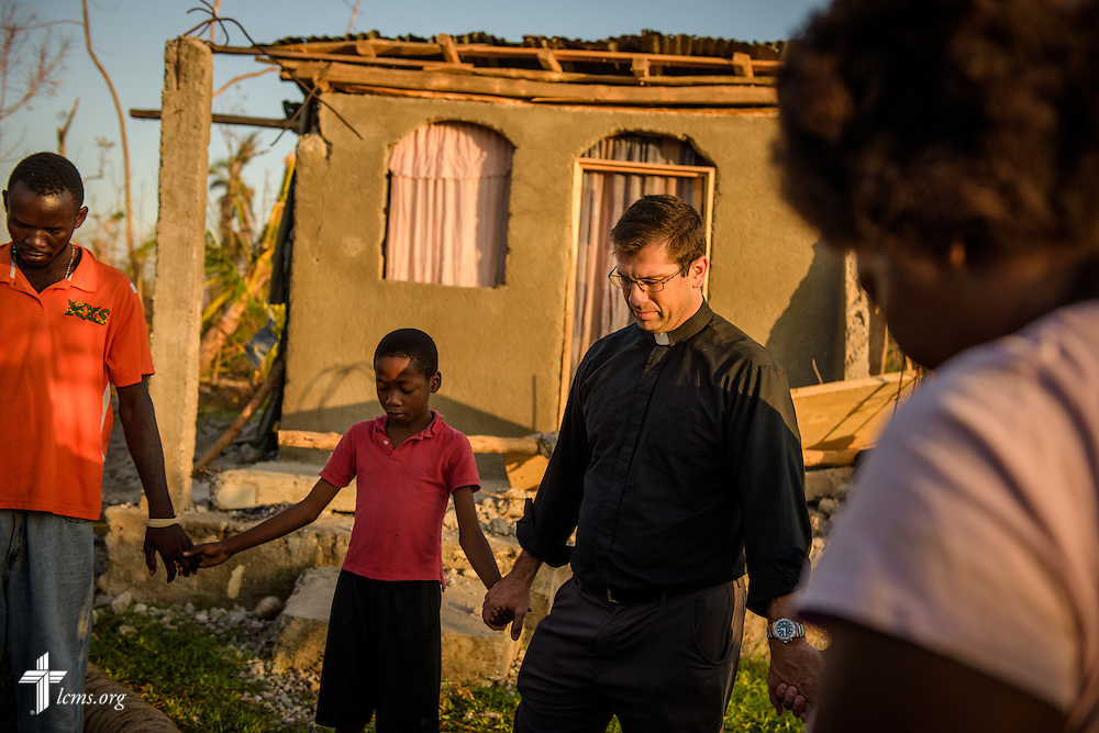 The Rev. Ross Johnson, director of LCMS Disaster Response, prays with a family outside a home severely damaged by Hurricane Matthew on Wednesday, Oct. 12, 2016, in a rural area of Les Cayes, Haiti. The family was part of the local Lutheran parish, which was also severely damaged in the storm. LCMS Communications/Erik M. Lunsford
