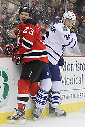 Mar 23; Newark, NJ, USA; New Jersey Devils right wing David Clarkson (23) is hit by Toronto Maple Leafs defenseman Carl Gunnarsson (36) during the second period at the Prudential Center.