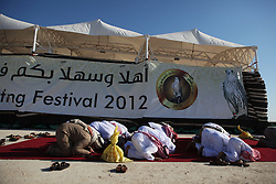 A group of men take a break from watching the falcon competition to take part in the midday Friday prayer.