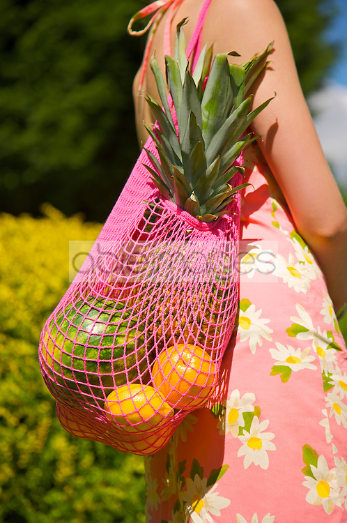 Woman carrying a shopping bag full of fruit - headless