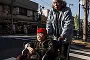 Kawasaki, November 21 2014 - Japanese artist Tatsumi ORIMOTO, 69, having a walk outside with his 97-year-old mother.