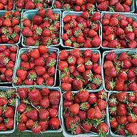 "Quarts of strawberries line the table of Morning Dew Orchards' stand. ""Pile em' high and let them fly,"" Woolf says."
