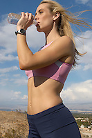 Female jogger drinking from water bottle, outdoors
