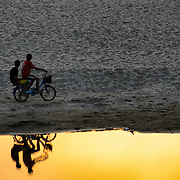 Two young boys on a bicycle stop to watch the sunset. on a sandbank in the Mekong River in Vientiane, Laos. As they do so, they're silhouetted against against still water in the bottom of the frame.
