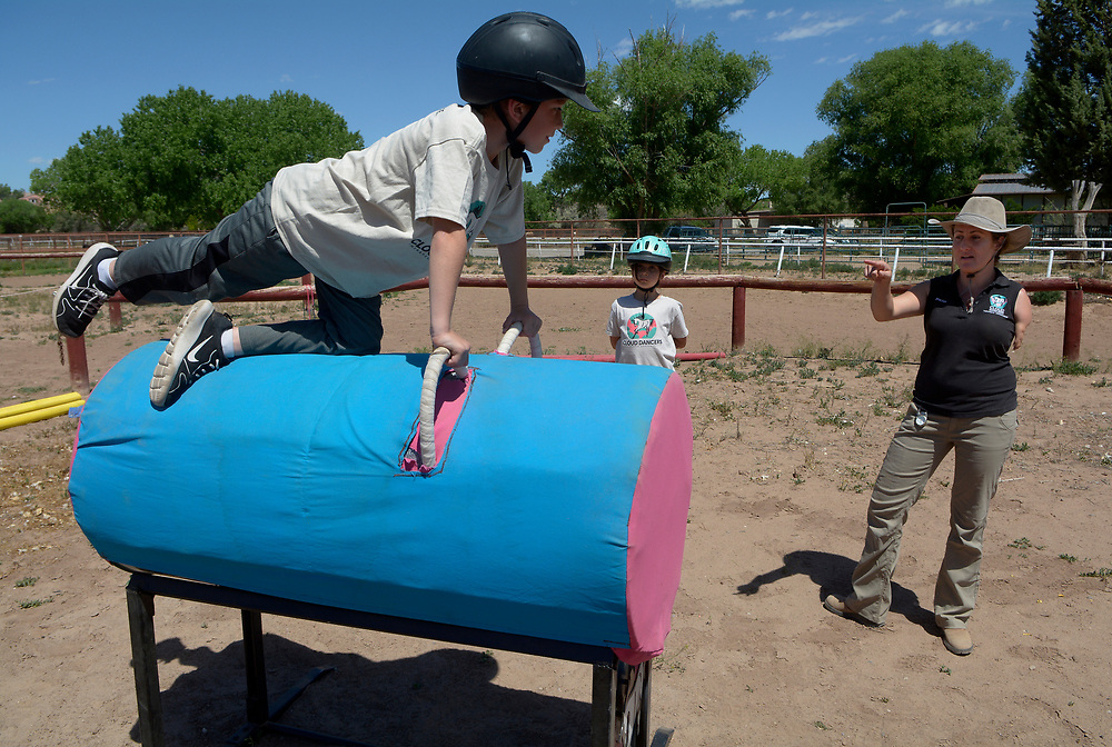 "gbs050717z/LIVING -- Horse vaulting instructor Tasha Books of Albuquerque, right, explains a vaulting move to Matthew Fehr, 9, of Albuquerque, left, and Esmeralda  ""Esme""  Marquez-Chavez, 9, of Albuquerque, center, while on a practice barrel before getting on a horse. (Greg Sorber/Albuquerque Journal)"