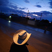 A man in a cowboy hat stands in the streets of Mexico under a cloudy evening sky.