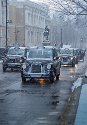 Black cabs make their way along Whitehall as a sudden, intense snow flurry arrives in Westminster. Westminster, London, February 27 2018.