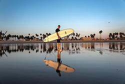 Jay Tanner heads in after a sunset wave in Venice Beach, California October 9, 2014. (Photo by Ami Vitale)