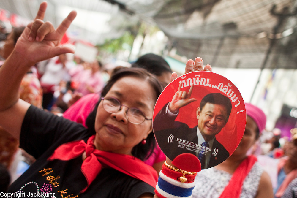 """May 12 - BANGKOK, THAILAND: A Red Shirt protester holds up a photo of exiled former Prime Minister Thaksin Shinawatra during the Red Shirt protest Wednesday. The Thai government said Wednesday that time has run out for """"Red Shirt"""" protesters in Ratchaprasong and Sala Daeng intersections in Bangkok and that a crackdown could come at any time. As news of the anticipated crackdown spread, Red Shirt protesters continued with an almost festive mood at their main stage but many of the sleeping areas around the protest site appeared to be empty. No official estimates on crowd size are available.  Photo by Jack Kurtz"""