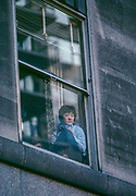 Girl with camera in window, watching parade, New York City, New York, USA