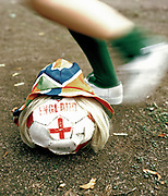 Blurred foot kicking football labeled with England.  UK, 2000's