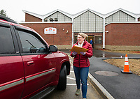 """Student Outreach Coordinator Hillary Ayers hands out student packets during the drive thru """"pick up"""" at Elm Street School on Friday.  (Karen Bobotas/for the Laconia Daily Sun)"""