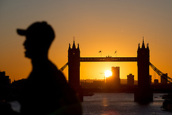 © Licensed to London News Pictures. 12/02/2018. London, UK. A jogger runs past the sunrise over Tower Bridge in central London this morning, as temperatures in the capital dropped to freezing overnight. Photo credit : Tom Nicholson/LNP