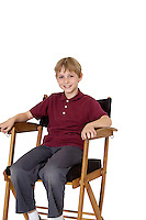 Portrait of a happy pre-teen boy sitting on director's chair over white background