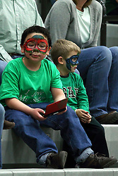 21 February 2015:  A pair of young fans with painted faces, one playing a game boy during an NCAA women's division 3 CCIW basketball game between the Elmhurst Bluejays and the Illinois Wesleyan Titans in Shirk Center, Bloomington IL