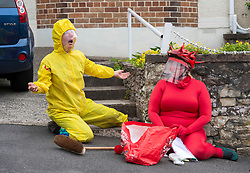 """© Licensed to London News Pictures; 26/07/2020; Bristol, UK. """"Hazmat"""" (in yellow) & """"Covid"""" (in red) perform on the streets of St Annes in The Bristol Coddywomple with a colourful clown show created specifically for these times of the coronavirus pandemic. The comedy double act consists of the virus, Covid 19, who is naive and playful, and a bright yellow Hazmat suited character who attempts to 'control the virus'. The Bristol Coddywomple is an ambling celebration of street performance with more than 40 performance artists, entertainers and musicians taking ambling versions of their shows out into their local areas, giving them a chance to show off their talents to live audiences while venues remain shut due to the coronavirus Covid-19 pandemic and lockdown when much art and performance has been unable to take place in normal venues. This is the first one of its kind in the UK, with the Coddywomplers performers of many types performing on the streets following pre-mapped and publicised routes to entertain their neighbours as they pass through with music, circus and visual treats. Audiences can watch from their windows and doorways, or come outside to interact with the entertainers from their front yards. Photo credit: Simon Chapman/LNP."""