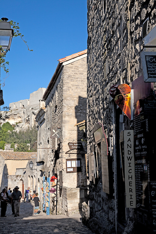 Typical narrow and steep shopping street in Les-Baux-de-Provence.  This ancient town has dominated its small mountain top since the 10th century.  Its narrow streets and tiny buildings now host numerous shops, eateries, and museums, and attract upwards of two million visitors annually.