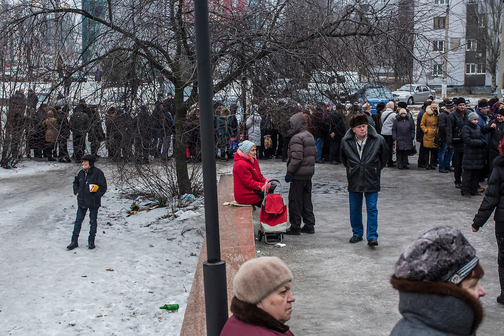 DONETSK, UKRAINE - JANUARY 29, 2015: People wait in line to receive food being distributed to needy residents by the Rinat Akhmetov Fund outside a supermarket in Donetsk, Ukraine. The food distribution drew heavy crowds as many people are no longer paid a salary or have had difficulty accessing bank accounts. CREDIT: Brendan Hoffman for The New York Times