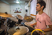 "31 MARCH 2013 - BANGKOK, THAILAND:     ""Sprite"" plays drums during Easter services at the Thai Peace Foundation office in the Bangkapi section of Bangkok.     PHOTO BY JACK KURTZ"
