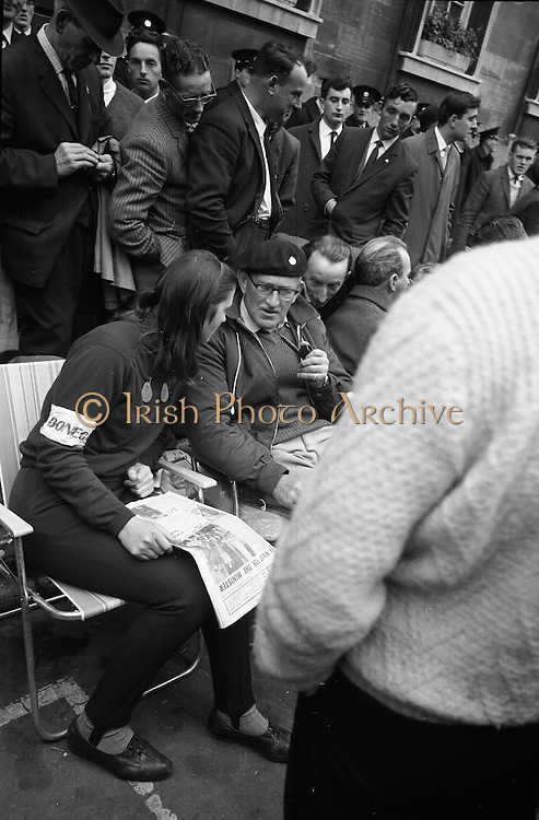 National Farmer's Association sit-down at Department of Agriculture. Rickard Deasy (with beret) seated at a camp of folding chairs on the edge of the road outside the Department of Agriculture, passes the time by reading the newspaper and chatting with sympathisers..20.10.1966